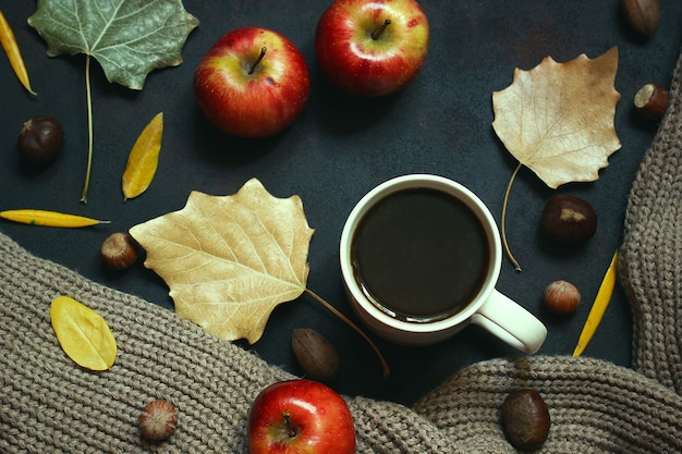 Autumn, fall leaves, hot steaming cup of coffee and a warm scarf or cardigan. seasonal, morning coffee, sunday relaxing and still life concept. Free Photo