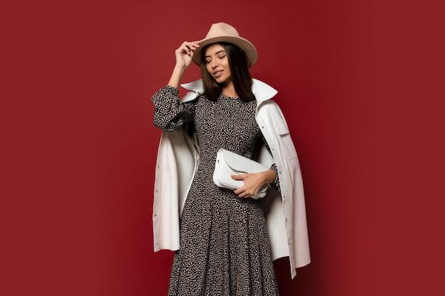 Look alla moda autunnale. splendida ragazza bruna europea in giacca bianca alla moda e vestito con stampa in posa. tenendo la borsa in pelle. Foto Gratuite