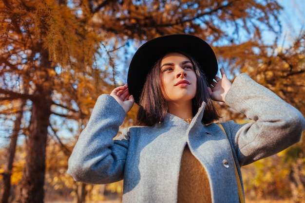 Autumn fashion. young woman wearing stylish outfit and holding hat outdoors. clothing and accessories Premium Photo