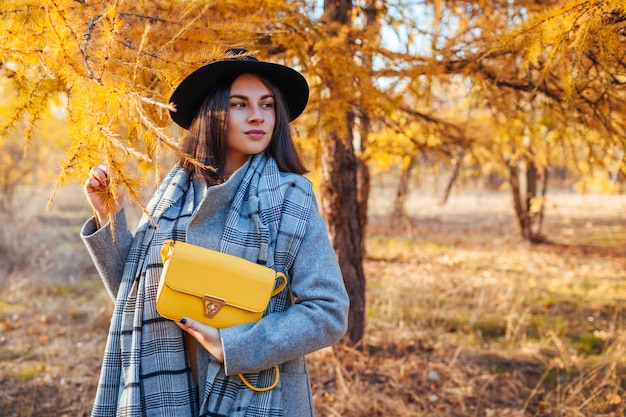 Autumn fashion. young woman wearing stylish outfit and holding purse outdoors Premium Photo