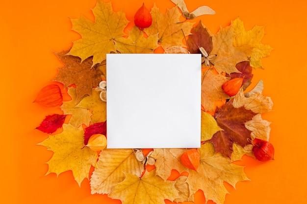 大胆なオレンジ色の空白のノートと乾燥した葉を持つ秋のフラットレイ構成 Premium写真