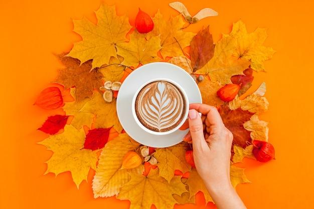 女性の手に乾燥した葉の花輪フレームとコーヒーラテカップと秋のフラットレイ構成 Premium写真
