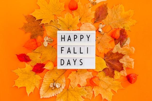 乾燥した葉の花輪フレームとライトボックスメッセージと秋のフラットレイ構成大胆なオレンジ色の背景に幸せな秋。創造的な秋の感謝祭の秋のハロウィーンのコンセプト。上面図、コピースペース Premium写真