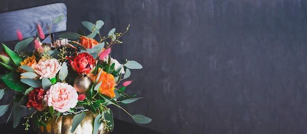 Autumn floral bouquet in punpkin vase on black chair, banner Premium Photo