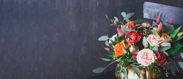 Autumn floral bouquet in punpkin vase on black chair, banner Premium Photo