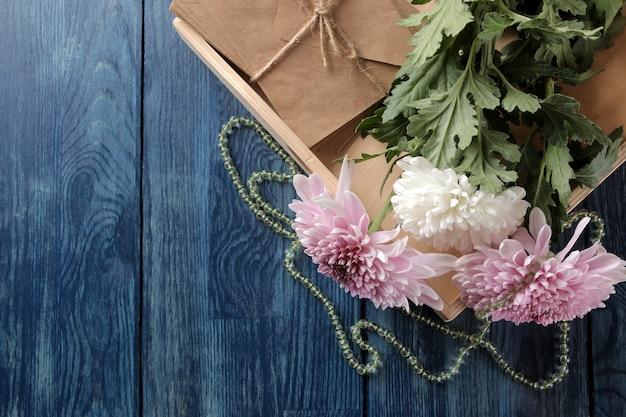 Осенние цветы хризантемы с бисером и буквами на синем столе с местом для надписи. Premium Фотографии