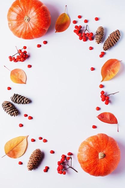 Autumn frame with leaves, rowan berries, orange pumpkins, pine cones on pastel background, flat lay Premium Photo