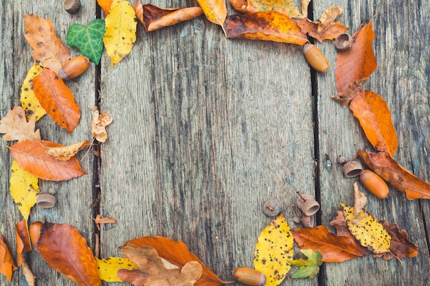 秋のフレーム。端にカラフルな葉を持つ木製のヴィンテージの背景。 Premium写真