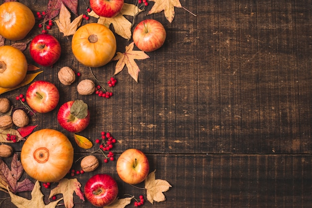 Autumn fruit and leaves on wooden background Free Photo