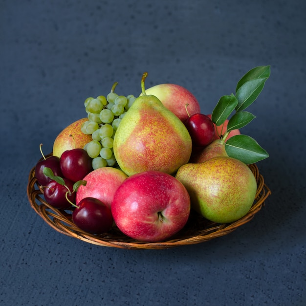 Autumn fruit mix in a wicker wooden plate. Premium Photo