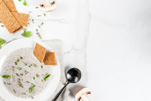 Autumn hot dishes. vegan soups. mushroom cream soup with brown fried champignons and herbs, thyme. on a white marble table. copyspace top view Premium Photo