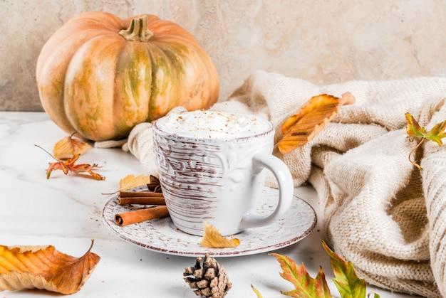 Осенние горячие напитки. тыквенный латте со взбитыми сливками, корицей и анисом на белом мраморном столе, со свитером, осенними листьями и еловыми шишками. Premium Фотографии