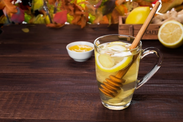 Autumn hot tea warming drink with ginger, honey and lemon in glas Premium Photo