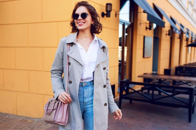 屋外を歩くベージュのコートを着たスタイリッシュな魅力的な女性の秋のイメージ。おしゃれなストリートルック。 無料写真