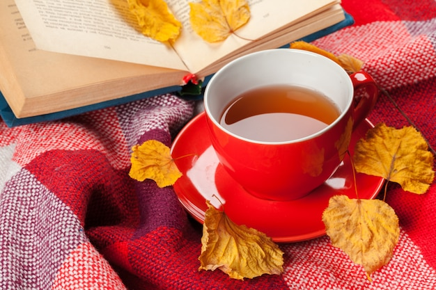 Autumn leaves, book and cup of tea Premium Photo