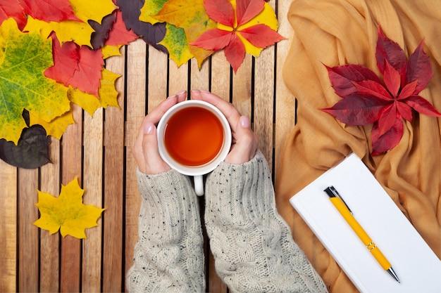 紅葉、白いノート、ペン、ニットセーターの女性の手でティーカップ、テキスタイルナプキン、木製の背景、モックアップ、テキストの場所 Premium写真