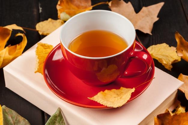 Осенние листья с книгой и чашкой чая Premium Фотографии