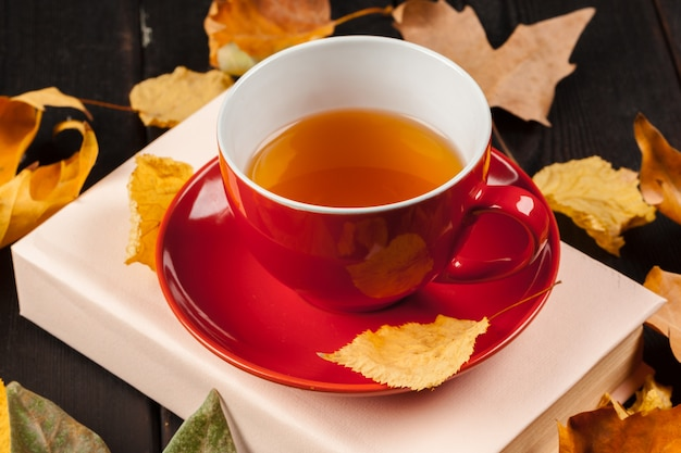 Autumn leaves with book and cup of tea Premium Photo