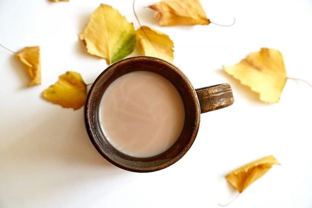 Autumn leaves with coffee or tea cup on white Premium Photo