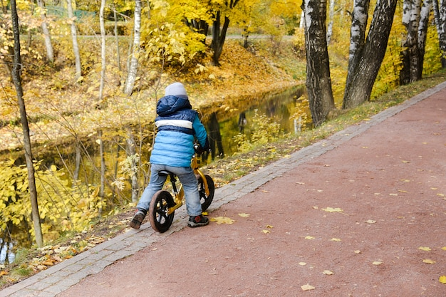 Autumn. a little boy rides a bike along a path in the park near the river. he rides on the edge of the cliff. Premium Photo