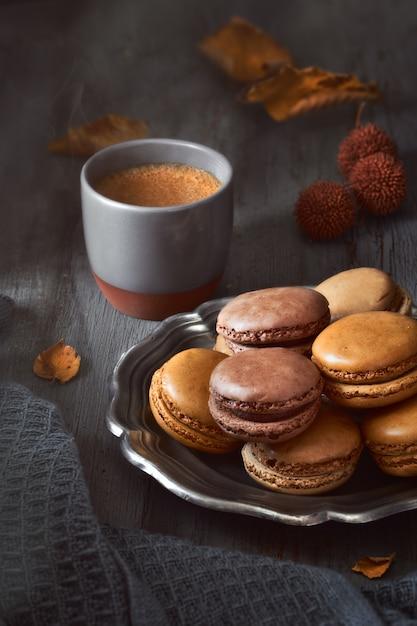 Autumn macarons with coffee on dark rustic wood Premium Photo