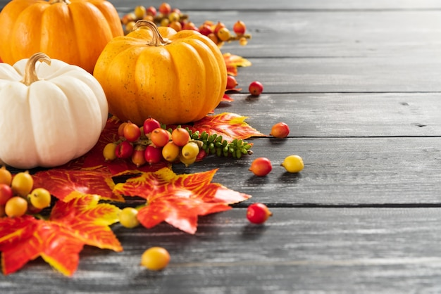 Autumn maple leaves and pumpkin on old wooden background. thanksgiving day concept. Premium Photo