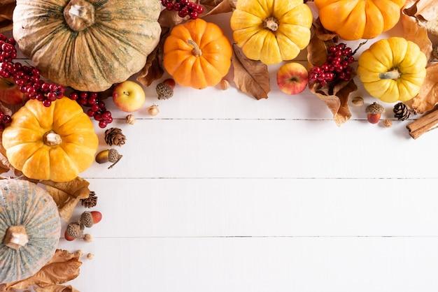 秋のカエデの葉、カボチャと赤い果実、感謝祭の日の概念。 Premium写真