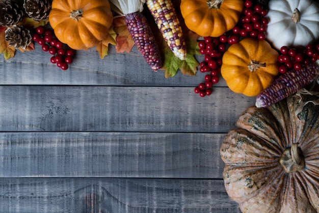 Autumn maple leaves with pumpkin, corn and red berries Premium Photo