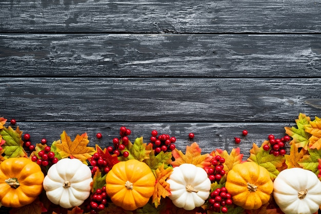 Autumn maple leaves with pumpkin and red berries on old wooden background. Premium Photo