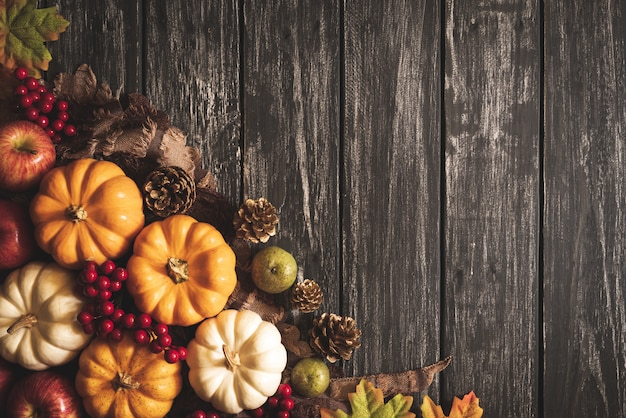 Autumn maple leaves with pumpkin and red berries on old wooden. thanksgiving concept. Premium Photo