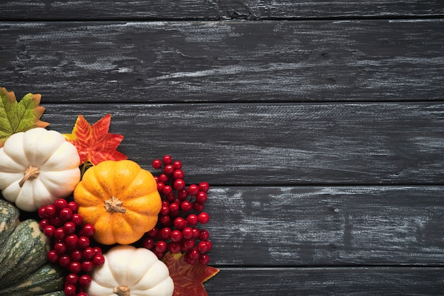 Autumn maple leaves with pumpkin and red berries on old wooden. Premium Photo