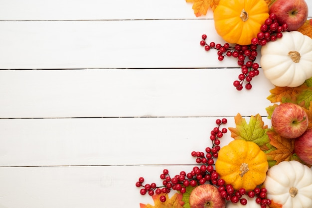 Autumn maple leaves with pumpkin and red berries on white wooden. thanksgiving day concept Premium Photo