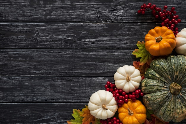 Autumn maple leaves with pumpkin and red berries on wooden background. thanksgiving concep Premium Photo