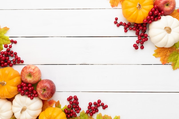 Autumn maple leaves with pumpkin and red berries on wooden background. Premium Photo