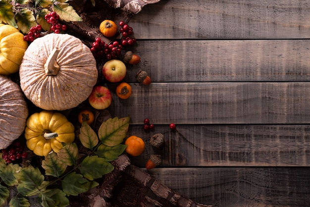 Autumn maple leaves with pumpkin on wooden background. thanksgiving concept. Premium Photo