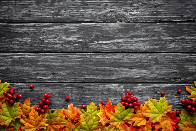 Autumn maple leaves with red berries on old wooden background. thanksgiving day concept. Premium Photo