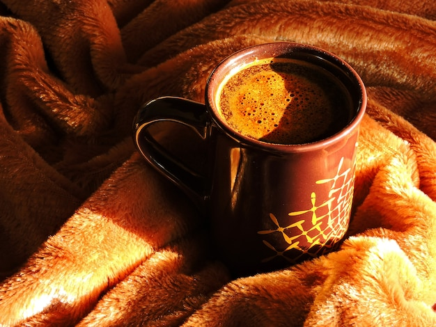 Autumn mood. a cup of coffee on a brown plaid. Premium Photo