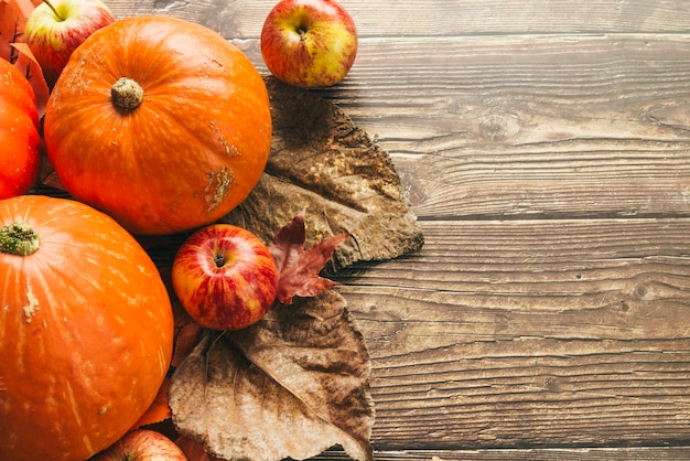 Autumn pumpkins on wooden table with leaves Free Photo