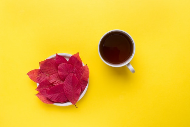 Autumn red leaves and a cup of coffee on a bright yellow background Premium Photo