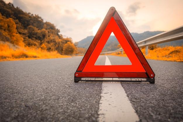 秋の道路赤い三角形、赤い緊急停止の標識、道路上の赤い緊急シンボル。 Premium写真