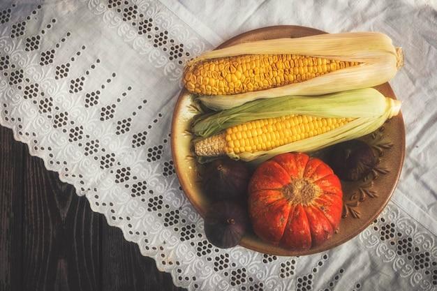 Осенний натюрморт в деревенском стиле с тыквой, кукурузой и инжиром на белой скатерти с кружевом Premium Фотографии