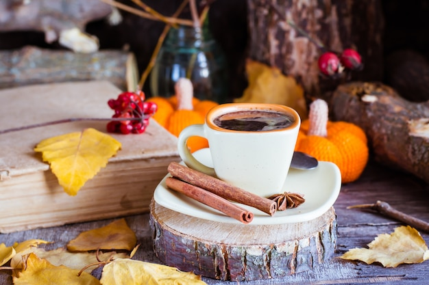 Autumn still life with coffee drink. a cup of black coffee and cinnamon on a cut of a tree. Premium Photo