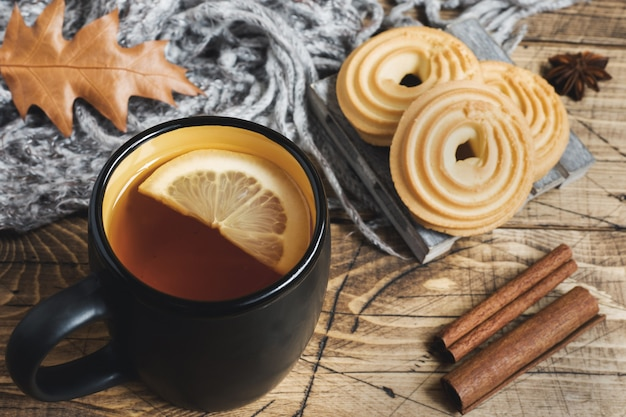 Autumn still life with cup of tea, cookies, sweater and leaves on wooden table. Premium Photo