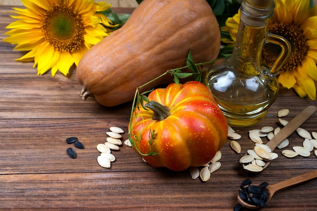 Autumn still life with pumpkins, oil and sunflowers Premium Photo