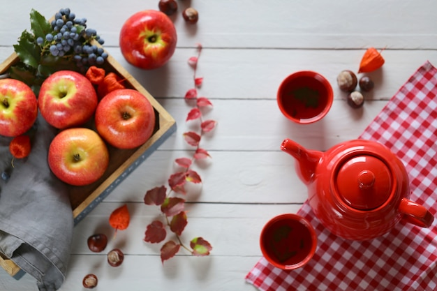 Autumn tea. teapot with a cup of tea on a blue wooden background Premium Photo