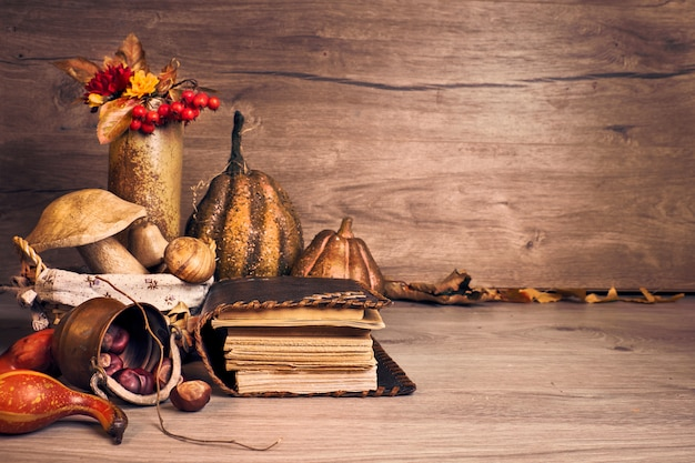 Autumn thanksgiving arrangement with wooden mushrooms, decorative pumpkins, fall leaves, apples, peppers and chestnuts. autumn still life arrangement indoors, old antique books on aged wooden table. Premium Photo
