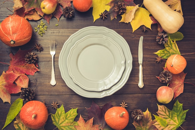 Autumn and thanksgiving day table setting with fallen leaves, pumpkins, spices, grey plate and cutlery on brown wooden table. top view, . Premium Photo