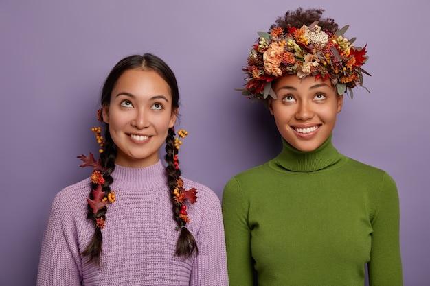 Концепция осеннего времени. веселые молодые разнорасовые девушки, одетые в повседневную одежду, сфокусированные наверху, имеют зубастые улыбки, носят в волосах осенние листья и ягоды, радуются осенним скидкам, позируют в помещении Бесплатные Фотографии
