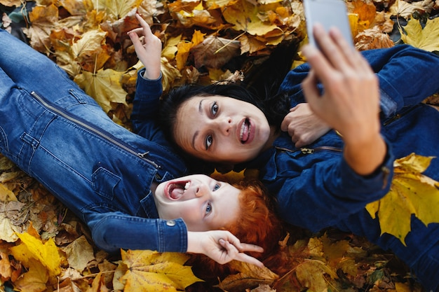 Autumn vibes, family portrait. charming mom and her red hair daughter have fun taking a selfie on sm Free Photo