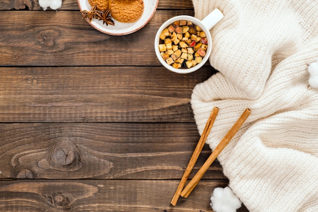 Autumn or winter composition. cup of herbal tea, women fashion white sweater, cinnamon sticks, cotton on wooden background Premium Photo